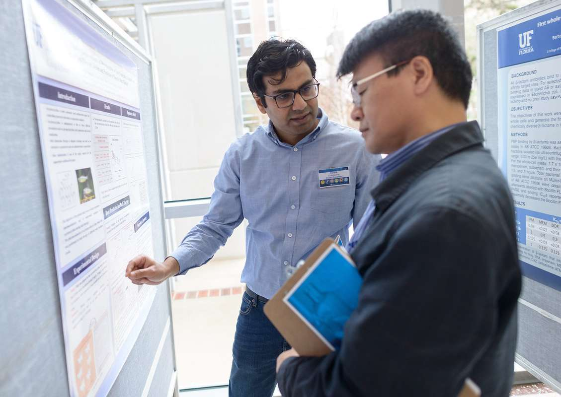 Students and faculty engaging in poster presentations for 31st Annual University of Florida College of Pharmacy Research Showcase.